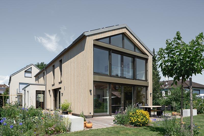 Der zweigeschossige Teil des Hauses ist mit einer vorgehängten Holzfassade versehen. Eine silikatische Vergrauungslasur simuliert eine vergraute, patinierte Oberfläche, wie sie durch eine mehrjährige Bewitterung auf Naturholz entsteht. Foto: Daniel Vieser. Architekturfotografie