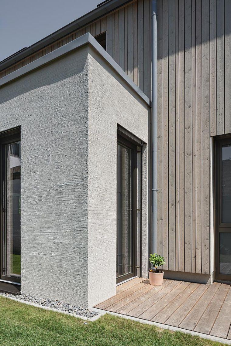 Ein waagerecht in Besenstrichoptik aufgetragener mineralischer Putz bildet den Abschluss eines mineralischen Dämmsystems für die Gebäudestruktur aus Beton, die senkrechte Holzverschalung passt sich farblich an. Foto: Daniel Vieser. Architekturfotografie