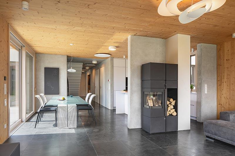 Ziel der Bauherren war es, den Charakter verschiedener Baustoffe zu zeigen. Sie kombinierten Holz und Beton so ausgleichend, dass ein komfortables Raumgefühl entstand. Der Boden aus Schiefer passt hervorragend zu dieser Kombination. Foto: Daniel Vieser. Architekturfotografie
